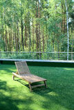 Wooden lounge chair on grass near  birchwood. A wooden lounge chair on a green grass near a birchwood Stock Photography