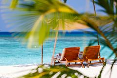 Tropical beach. Wooden lounge chairs on a beautiful tropical beach at Maldives Royalty Free Stock Photo