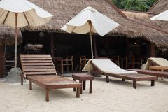 Wooden lounge chairs with palm leaves house at Thailand. Photo take on 2018 Royalty Free Stock Images