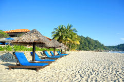 Wooden lounge / deck chairs and umbrella on paradise beach looking out to ocean. Blue sky Royalty Free Stock Photography
