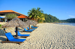 Wooden lounge / deck chairs and umbrella on paradise beach looking out to ocean. Blue sky Royalty Free Stock Photos