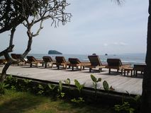 Wooden seaside deck with lounge chairs. Wooden lounge deck with unoccupied lazy chairs with sea view right next to the shore in island Bali stock photography