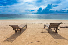 Lonely beach. Wooden lounger on lonely beach in the tropics Stock Photography