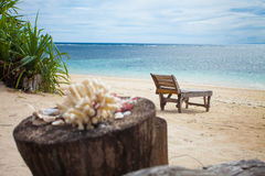 Lonely beach. Wooden lounger on lonely beach in the tropics Royalty Free Stock Image