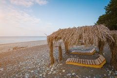 Wooden lounges and awnings with a cane roof on the seashore.  royalty free stock photo