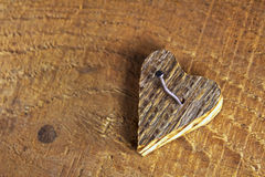 Wooden heart nailed on wooden background Stock Images