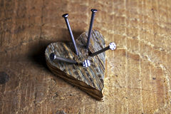 Wooden love heart pierced by nailes Stock Images