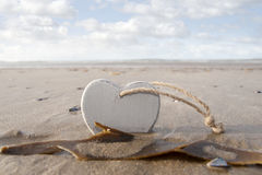 Wooden love heart in the sand Royalty Free Stock Images