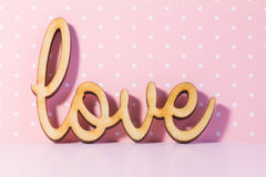 Wooden Love inscription on pink background Stock Photography