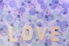 Wooden love letter on the violet floral gift wrapped paper as background with copy space. Or use as wallpaper. Love photo concept royalty free stock photography