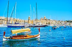 The wooden luzzu boat, Birgu, Malta. The lonely luzzu boat in front of the moored yachts in Vittoriosa marina and medieval Birgu on the opposite shore, Malta royalty free stock image
