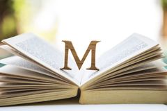 Wooden M font design on open old book over blurred background stock photography