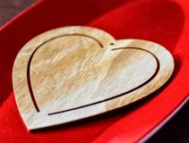 Wooden heart on a red shinny tray royalty free stock photo