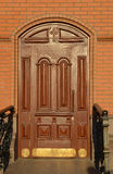 Wooden mahogany door in a brick wall Royalty Free Stock Images