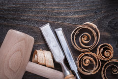 Wooden mallet chisels and curled up planing chips on vintage woo Royalty Free Stock Image