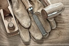 Wooden mallet planer chisel protective gloves on wood board.  Stock Photo