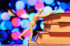 Wooden man climb up on pile of books. Education. And teaching concept Stock Photos
