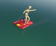 Wooden man on credit card is floating on the water. The wooden man on a credit card is floating on the water in the attitude of the surfer. 3D rendering Royalty Free Stock Photo