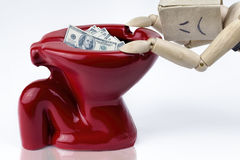 Wooden man depressed sitting on toilet bowl filled with cash