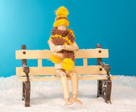 The wooden man figure on bench in the freezing. The wooden figure of a man on a bench in the freezing snow Stock Images