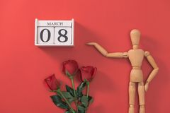 Wooden man figure with red flowers. Concept for valentine`s day. stock images