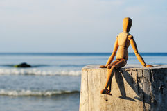 Wooden Man. Figurine of wooden man sitting on the stone at the sea Royalty Free Stock Images