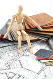 Wooden man, furnishing materials, blueprints Royalty Free Stock Photo
