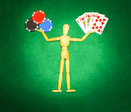 Wooden man with hands up to hold chips and cards for playing poker Stock Images