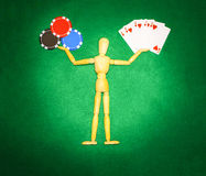 Wooden man with hands up to hold chips and cards for playing poker Royalty Free Stock Photo