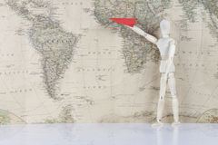 Wooden man holding airplane on world map Royalty Free Stock Images