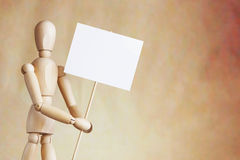Wooden man holding blank white poster in its hands Stock Images