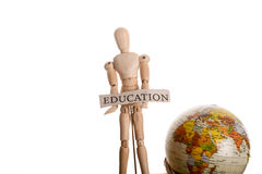 Wooden man holding education sign and globe. Wooden man holding education sign standing in front of a globe on a white background royalty free stock images