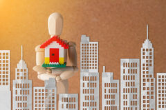 Wooden man holding home model and city shape paper cut.jpg Royalty Free Stock Image