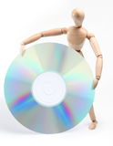 Wooden man holding a large computer disc. Stock Photos