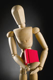 Wooden man holding red book. Stock Photo
