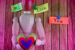 Wooden man holds in his hands the heart and in the background th Stock Photos