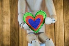 Wooden man holds in his hands the heart and in the background th Royalty Free Stock Photo