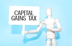 The wooden man holds a white sign with the text CAPITAL GAINS TAX in his hands. The content of the lettering has implications for