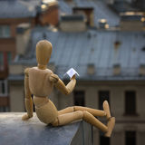 Wooden man launches a paper airplane from the roof in a big industrial city stock photography