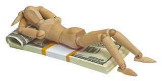 Wooden man lying on a pack of dollars. Are on the bed Royalty Free Stock Image