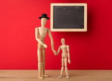 Wooden man mannequin with wooden child. Wooden mannequins as father and son symbols against red background. Education, upbringing, parents and children concept stock photography