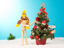 Wooden man near a Christmas tree Royalty Free Stock Images