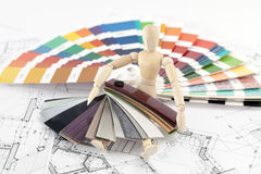 Wooden man and palette of colors Stock Photos