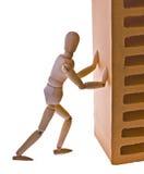 Wooden man pushes bricks Royalty Free Stock Photos
