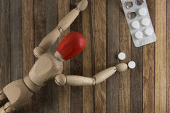 Wooden man with a red head headaches crawling to tablets stock photography
