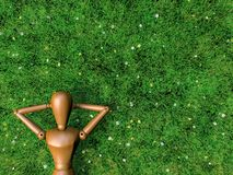 Wooden man is relax in filed of grass. Royalty Free Stock Images