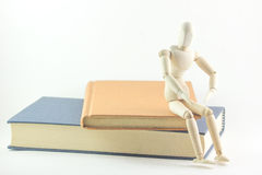 Wooden man sat on books Royalty Free Stock Photography