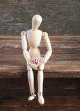 Wooden man sits in sorrow royalty free stock image