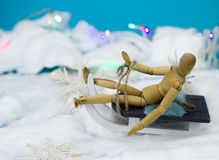 Wooden man on a sleigh. On blue background Royalty Free Stock Photography