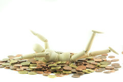 Wooden man swimming in money Stock Image